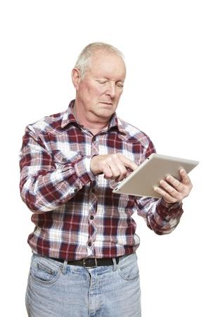 perplexing: Hombre mayor que usa el ordenador tableta mirando confundido sobre fondo blanco