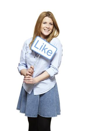 Jonge vrouw die een social media teken lachend op witte achtergrond Stockfoto