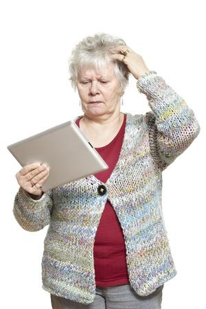 señora mayor: Mujer mayor que usa el ordenador tableta mirando confundido sobre fondo blanco Foto de archivo