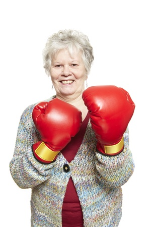 Senior woman wearing boxing gloves smiling on white background photo