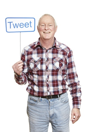 tweet: Senior man holding a social media sign smiling on white background