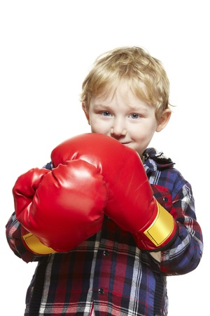 boy boxing: Young boy wearing boxing gloves smiling on white background