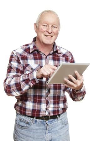 Senior man met behulp van tablet-computer glimlachen op witte achtergrond
