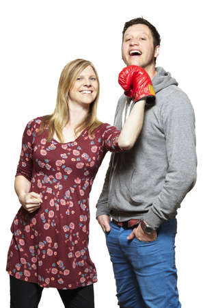 disagreed: Young couple fighting with boxing gloves smiling on white background