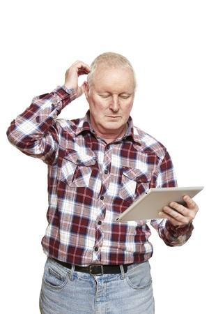 perplexing: Senior hombre con tablet PC en busca confundir sobre fondo blanco