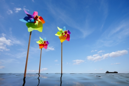 Toy windmill concept of green energy wind farm at sea photo