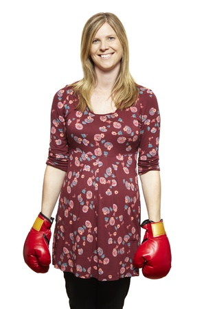 casually: Young woman wearing boxing gloves smiling on white background