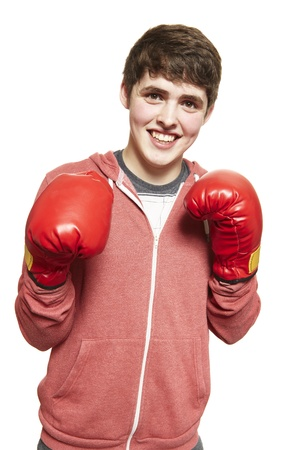 teenage male: Young teenage boy wearing boxing gloves smiling on white background