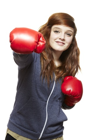 girl punch: Young teenage girl wearing boxing gloves smiling on white background
