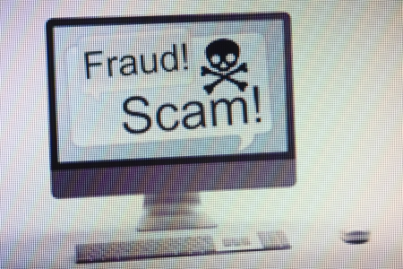 criminally: Desktop computer displaying conceptual internet fraud and scam warning on screen