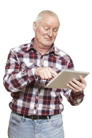 puzzling: Senior man using tablet computer looking confused on white background