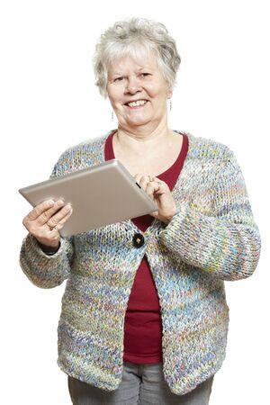 Senior vrouw met behulp van tablet-computer lachend op een witte achtergrond Stockfoto