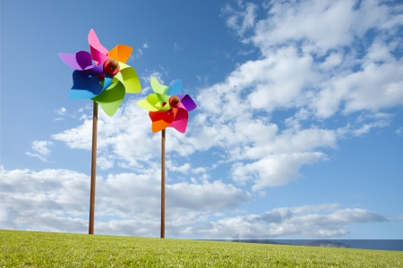 spinner: Toy windmill concept of green energy wind farm in field by the sea