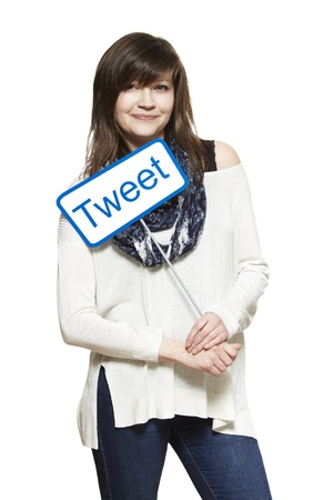 tweet: Young woman holding a social media sign smiling on white background