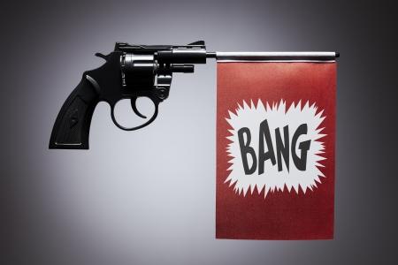firing: Gun crime concept of hand pistol showing a bang flag Stock Photo