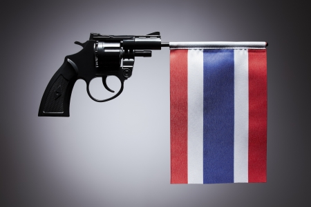 Gun crime concept of hand pistol showing the flag of thailand photo