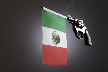 Gun crime concept of hand pistol showing the flag of mexico photo