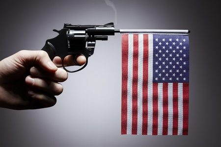 Gun crime concept of hand pistol showing the flag of united states of america photo