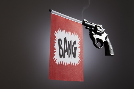 shootings: Gun crime concept of hand pistol showing a bang flag Stock Photo