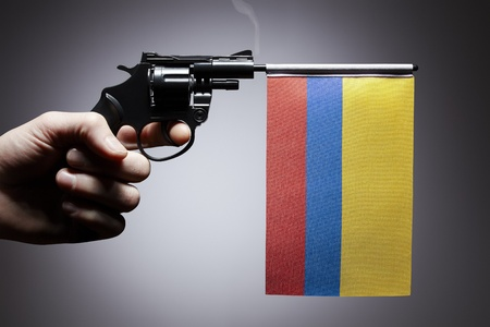 colombian: Gun crime concept of hand pistol showing the flag of colombia Stock Photo
