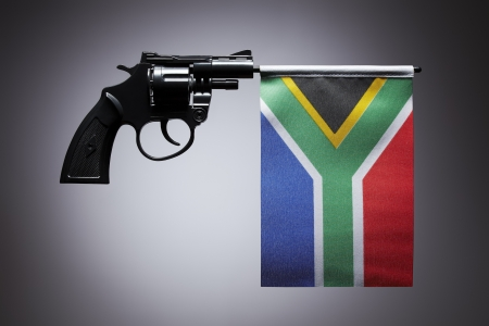 Gun crime concept of hand pistol showing the flag of south africa photo