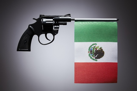 shootings: Gun crime concept of hand pistol showing the flag of mexico