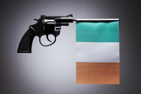 Gun crime concept of hand pistol showing the flag of ireland
