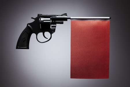 Gun crime concept of hand pistol showing a blank red flag photo