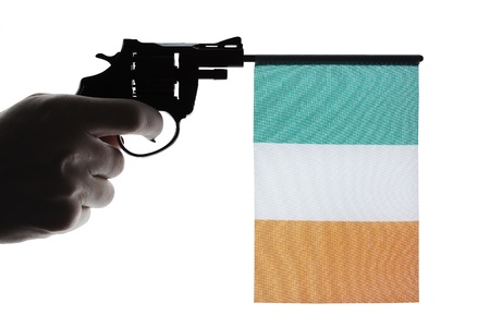 Gun crime concept of hand pistol showing the flag of ireland photo