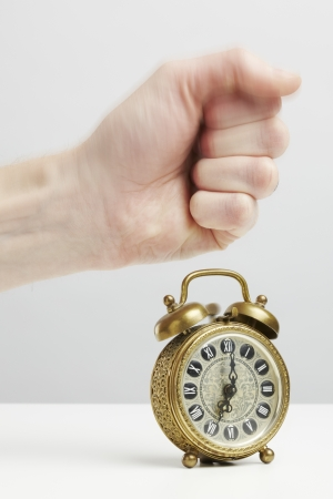 Hand stopping alarm on clock isolated plain background photo