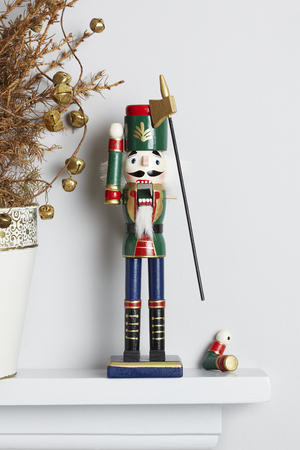 solider: Christmas nutcracker solider broken on mantle piece with decorated dead pine tree  Unhappy xmas concept Stock Photo