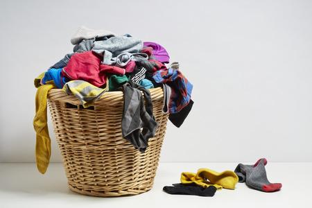 Cesta de la ropa que desborda. Concepto de tarea doméstica en el fondo blanco Foto de archivo - 26814619