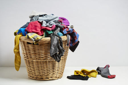 dirty clothes: Overflowing laundry basket. Household chore concept on white background Stock Photo