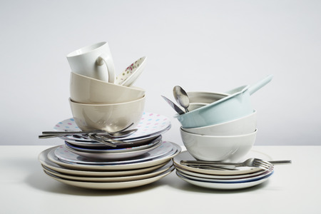 wash dishes: Platos sucios pila necesidad lavado. Concepto de tarea doméstica en el fondo blanco