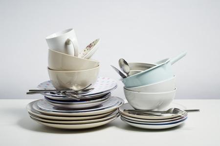 Vuile vaat stapel nodig afwas. Huishouden karwei concept op witte achtergrond