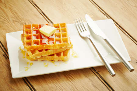 table top: Waffles with syrup on white dish and wooden table top
