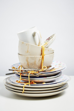 pile up: Dirty dishes pile needing washing up  Household chore concept on white background Stock Photo