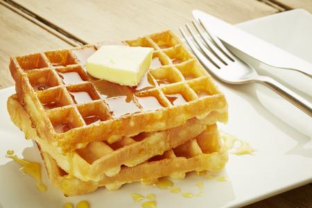 waffles: Waffles con jarabe en un plato blanco y madera mesa