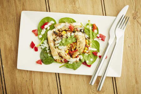 Chicken salad on white dish and wooden table top