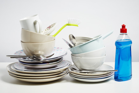tidying up: Dirty dishes pile needing washing up. Household chore concept on white background