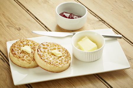 british food: Crumpets toasted on white dish and wooden table top