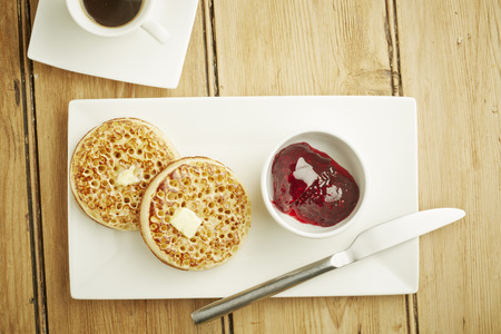jelly head: Crumpets toasted on white dish and wooden table top