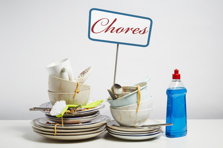 household chore: Dirty dishes pile needing washing up. Household chore concept on white background