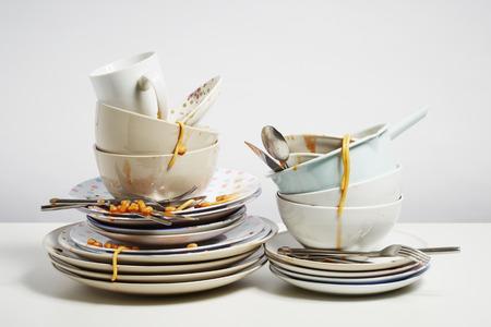 Špinavé nádobí pile potřebuje mytí nádobí. Domácnost fuška koncepce na bílém pozadí