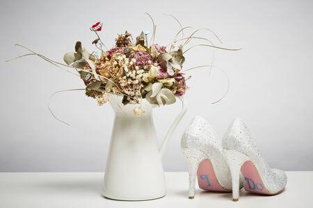 flores secas: Zapatos de novia y flores secas en el florero sobre la mesa blanca arriba