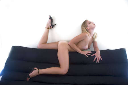 female nude posing on black couch Stock Photo