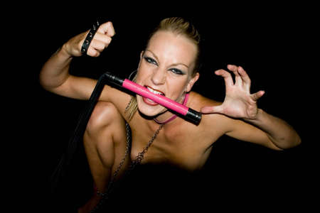 sexy blond female holding a whip in mouth