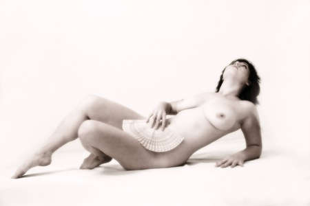 sexy nude female laying down holding a fan