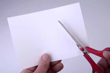 hand holding blank sheet of paper and cutting it with pair of scissors, background