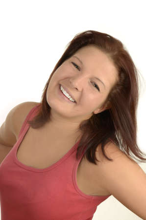 Young pretty woman in pink top smiling against white background, isolated, portrait photo